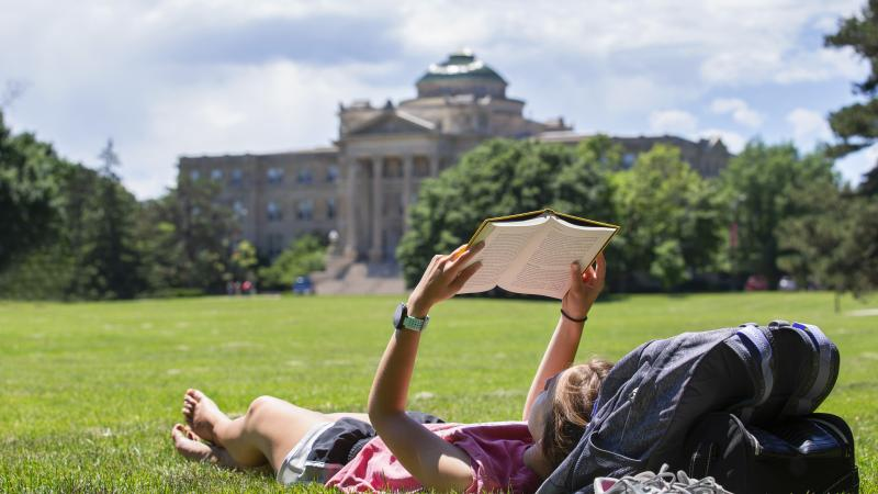 Student laying on sunny central campus while reading a book.