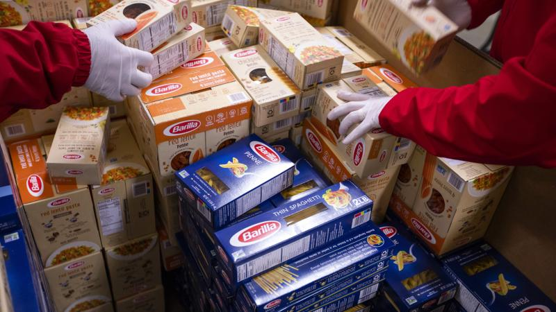 Gloved hands organize a container full of donated boxed pasta.