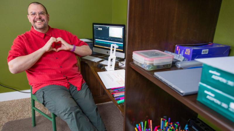 Mathematics associate professor Steve Butler uses his home office to conduct online instruction to his students. He is mindful to make it fun, delivered with warmth, and often expresses love for his students, sometimes making the heart symbol with his hands. Photos by Christopher Gannon.