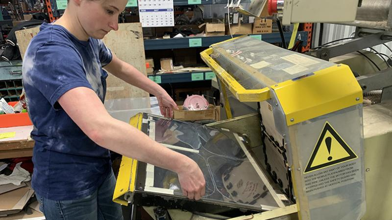 An employee of The Dimensional Group working on face shields at the company's Mason City plant
