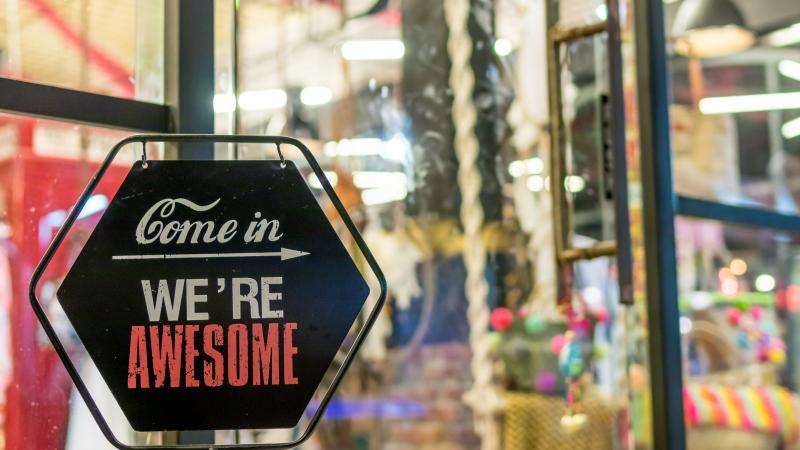 "Sign on a business door that reads ""Com in, We're Awesome."""