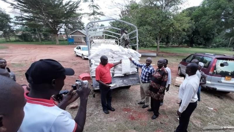 Gideon Nadiope, national director of the Center for Sustainable Rural Livelihoods-Uganda Program, helps deliver maize flour to the Kamuli District Task Force.