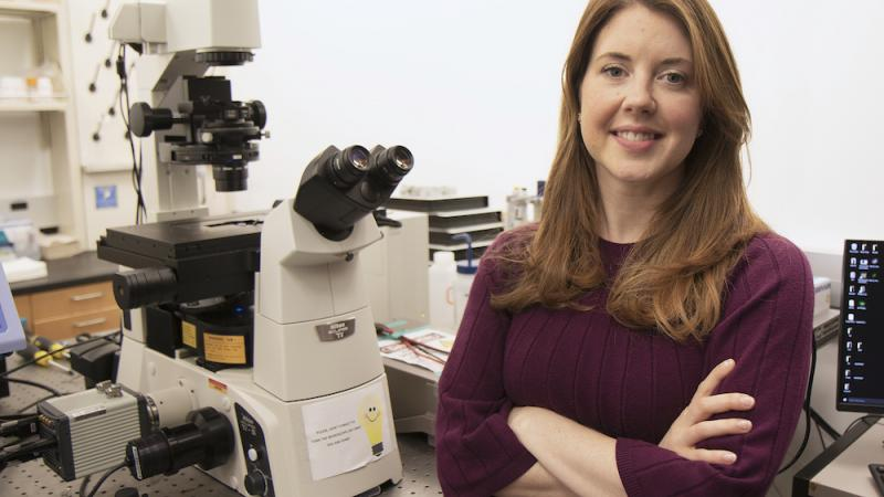 Researcher Robbyn Anand standing near a microscope