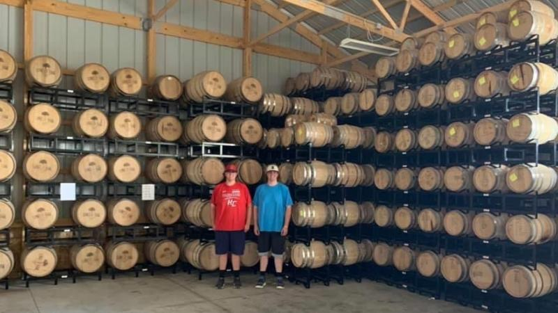 Two ISU students pose in front of shelves of whiskey barrels filled with hand sanitizer.