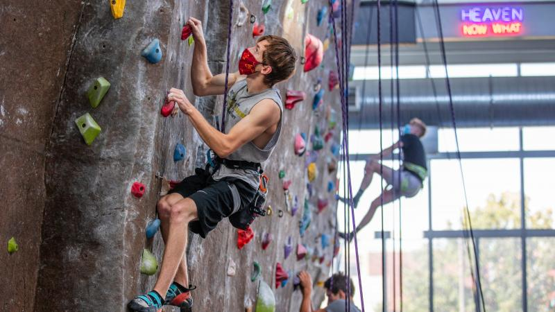 Three students scale the rock climbing wall in State Gym