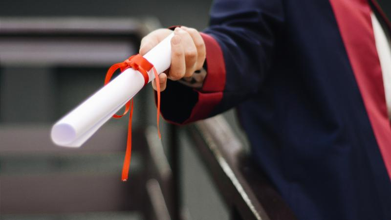 Closeup of a graduation diploma scroll being handed out