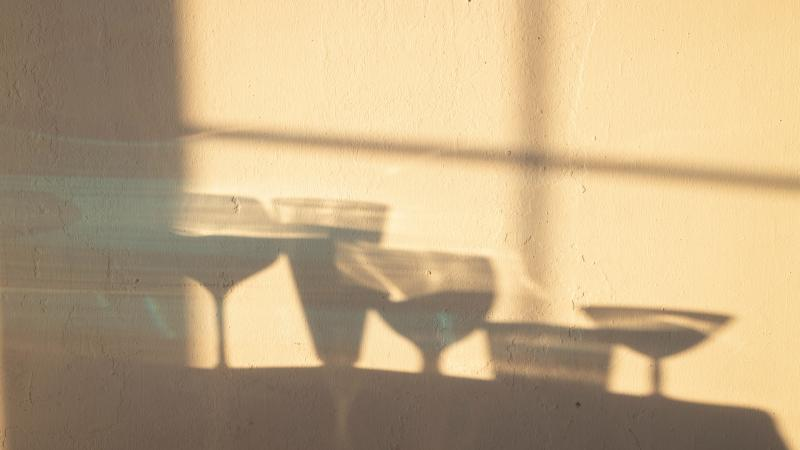 Shadows of drink glasses reflected on a wall