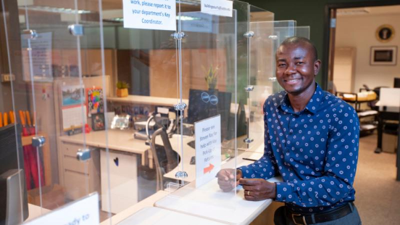 Ayodeji Oluwalana, recycling and special events coordinator for Facilities Planning and Management, with the plexiglass barriers that will soon be coming down inside the General Services Building.